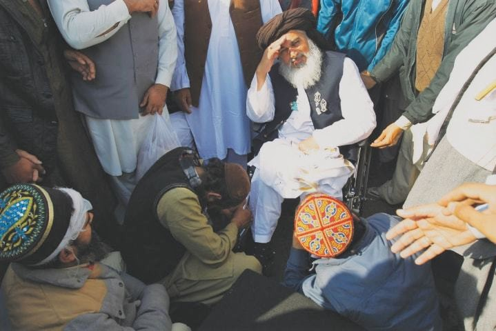 A supporter prays at the feet of Rizvi