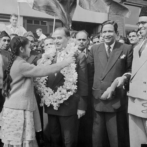 Huseyn Shaheed Suhrawardy (1892 - 1963), the Prime Minister of Pakistan, receives a garland from 12-year-old Jehanara Choudhry, upon his arrival at London Airport, 24th June 1957. Suhrawardy is in the UK to attend the Commonwealth Prime Ministers' Conference which opens the next day, 24th June 1957.
